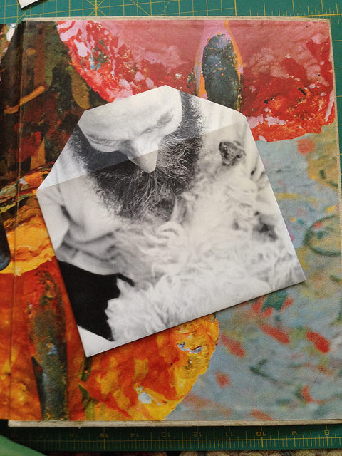 envelope with a man's face on it on top of a painting endpaper from an art book