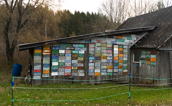 side of a barn entirely covered with license plates