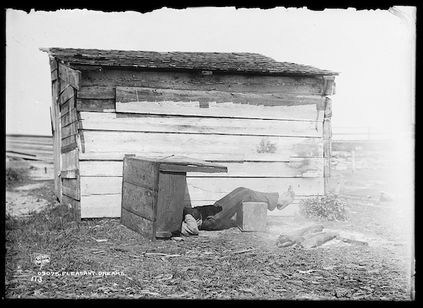 black and white image of a person asleep on their back in front of a little midwestern looking cabin
