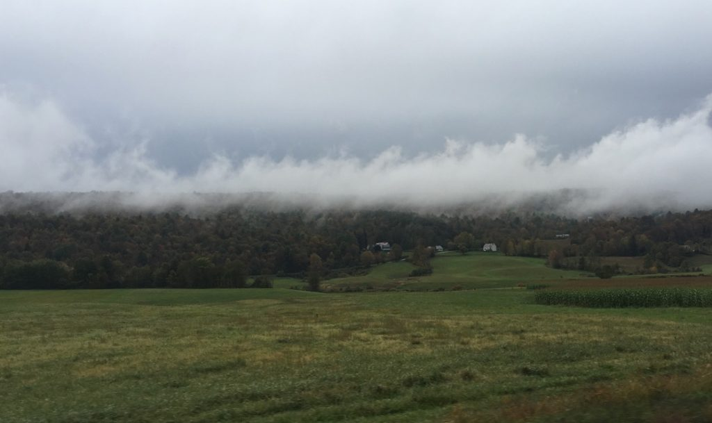clouds hanging over a rural farming valley