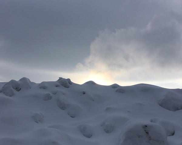 photo of a wallk of snow with the sun peeking out from behind it with some wispy clouds being lit by the sun.