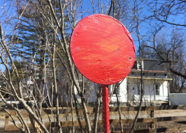 A color photo of a metal disc which is on top of fire hydrants so you can find them in the snow. It's painted a shiny red and is contrasted against the blue of the sky
