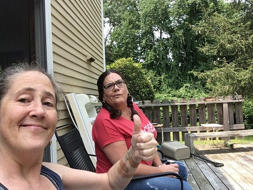 me and kate sistting on the back porch of my mom's house. I am making the thumbs up sign, she is making a face.