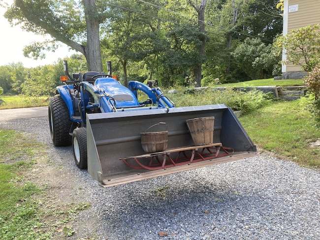 a blue tractor with the bucket holding two apple baskets and a sled