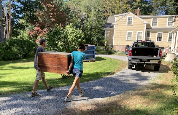 two people walking outside with a big cedar chest